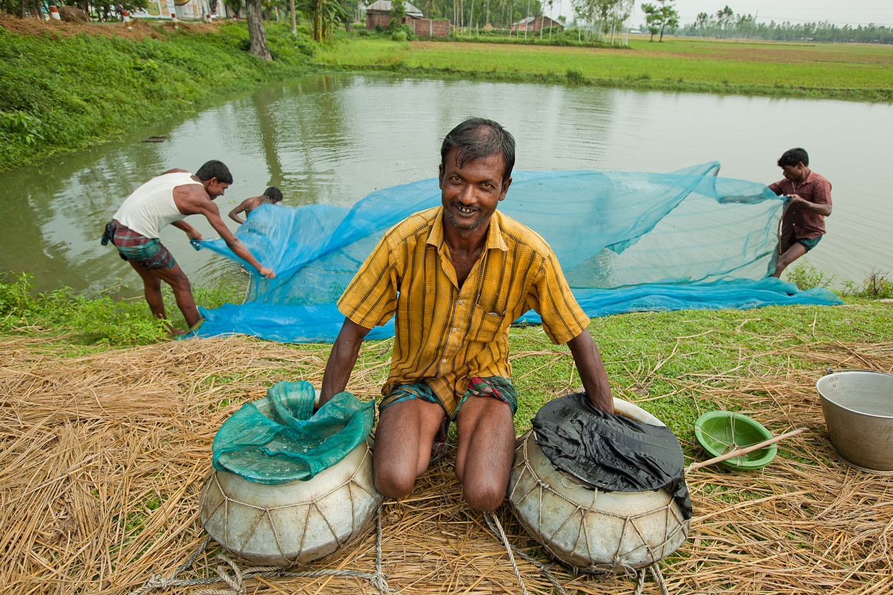 Indian fishermen on the bank of a lazy river.