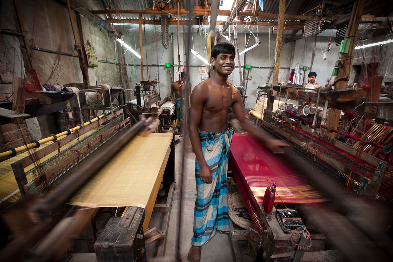 A young man works in a hot textile factory in India.