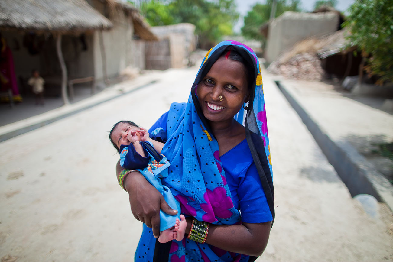 A new Indian mother proudly holds her young baby.