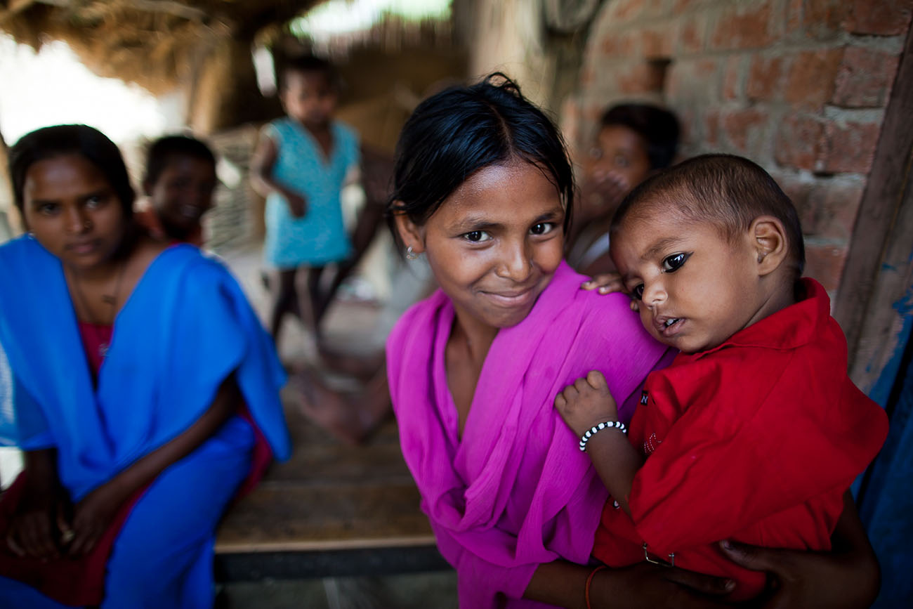 A group of young people in India await healthcare.