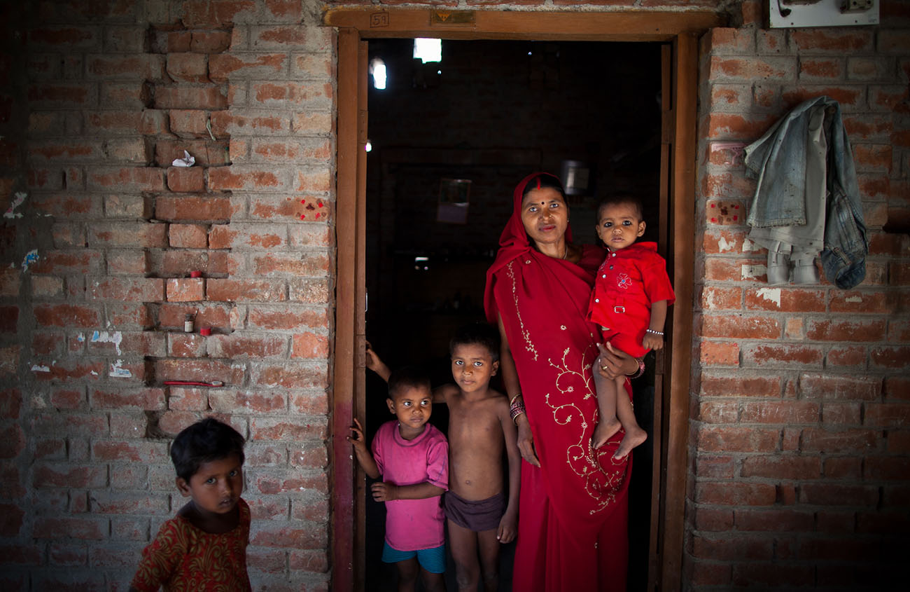 A young family in India stands in a doorway.