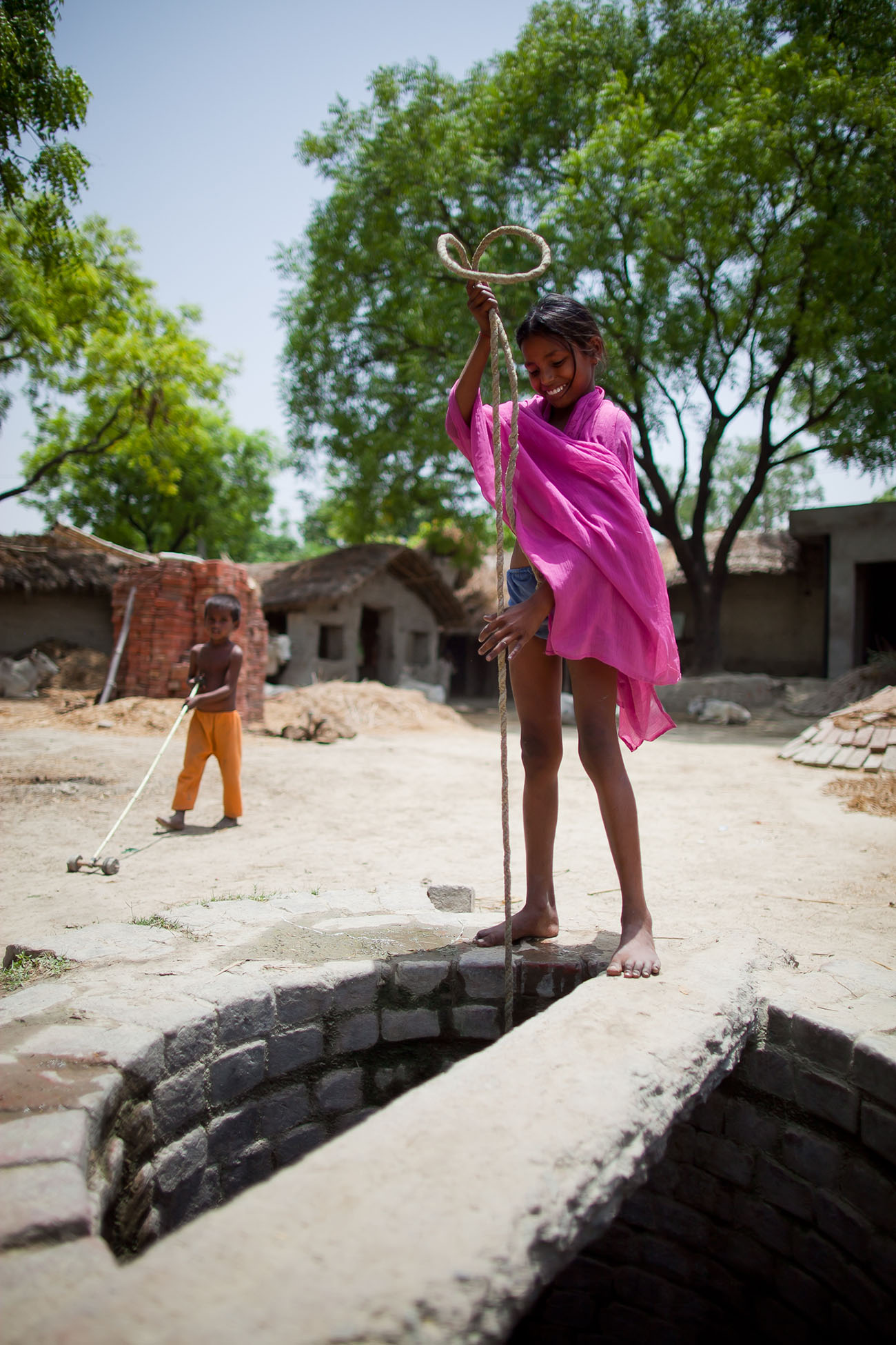 A young girl gets water from a well in India.