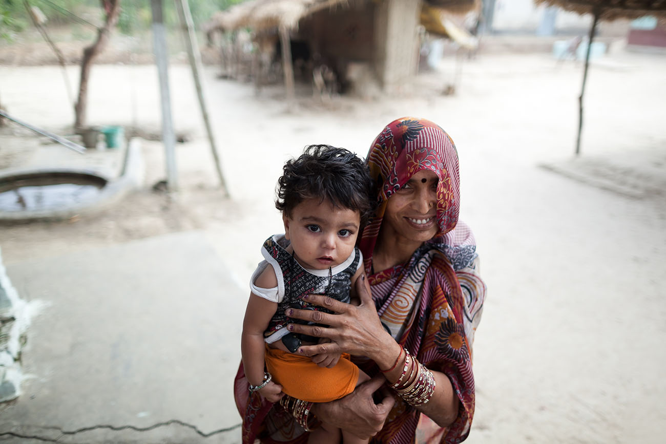 A mother in India smiles as she holes her baby.