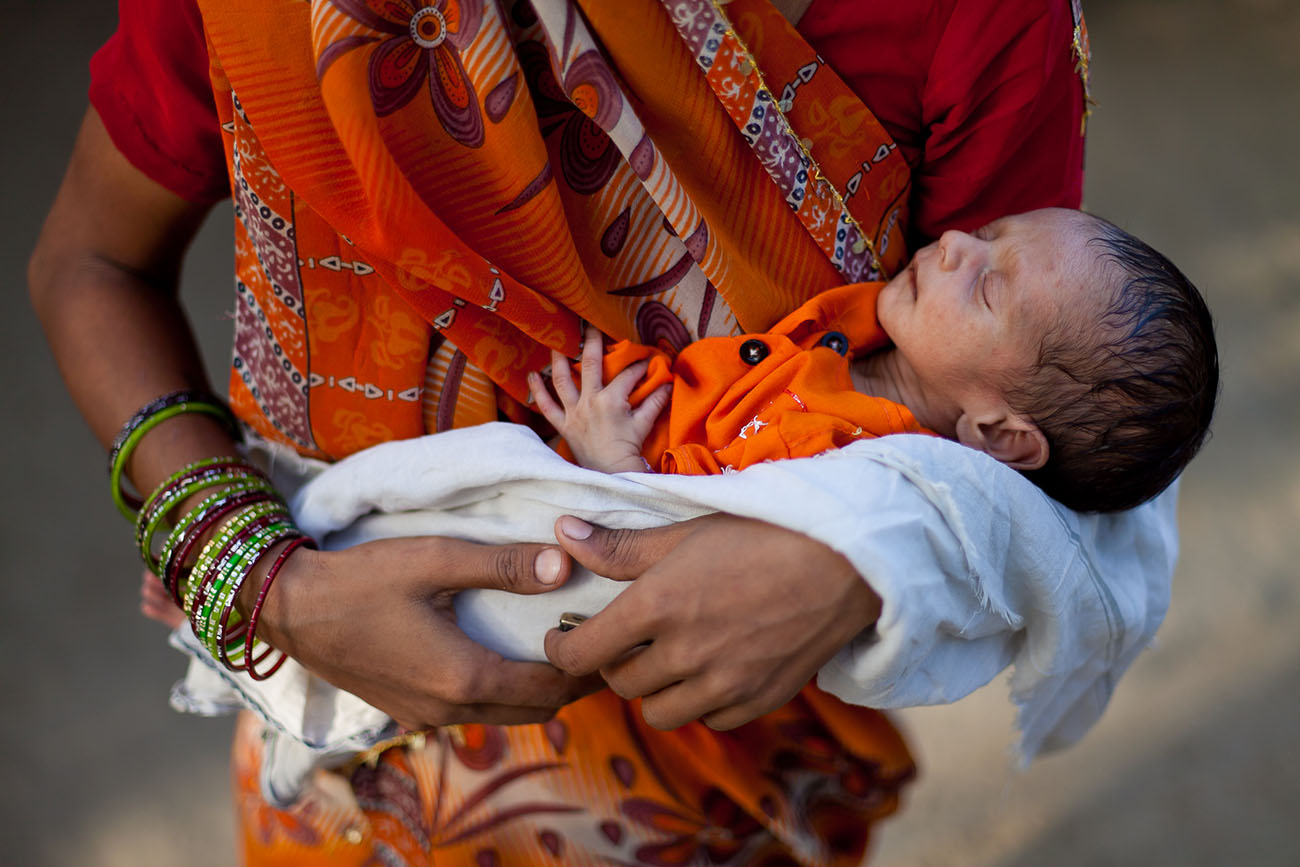 A newborn baby in his mother's arms in India.
