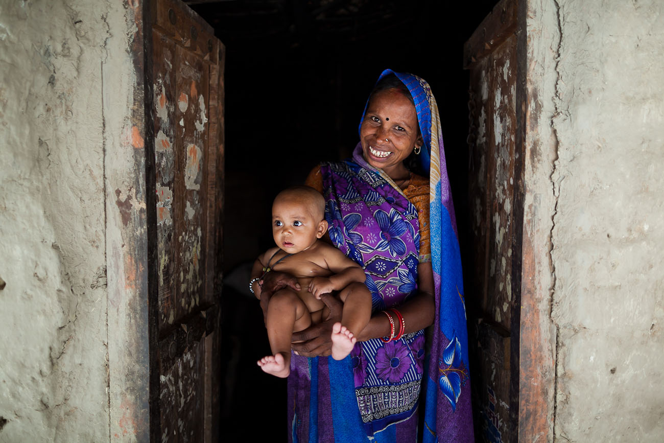 In India, a young mother happily holds her baby.