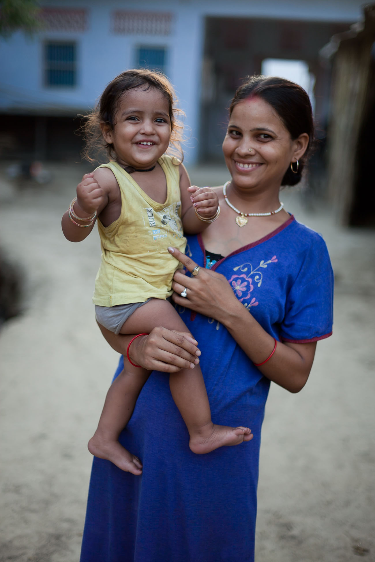 A happy young mother in India holds her child.