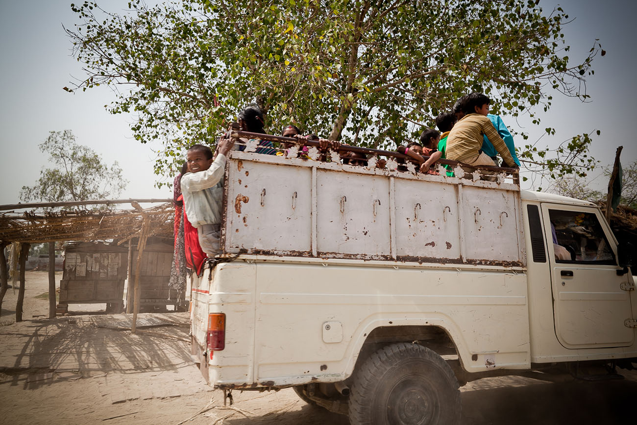 A truck filled with young Indians as it makes its way through a village.