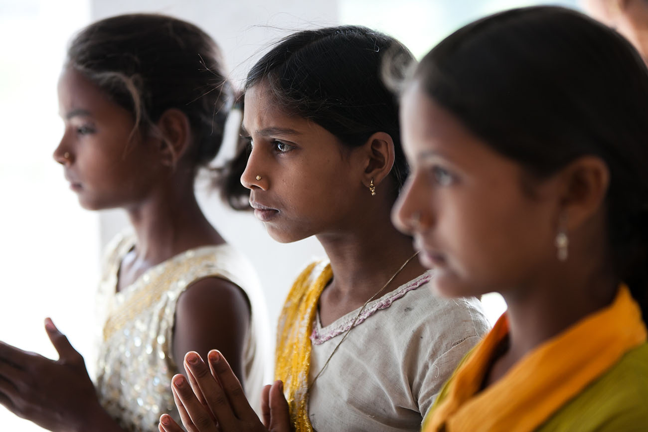 Young women in India praying.