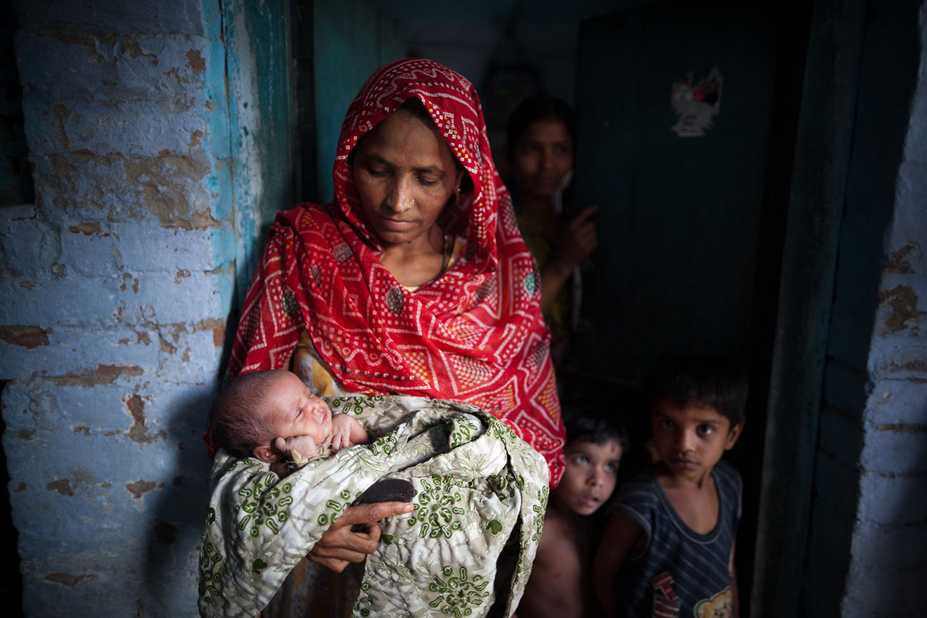 An Indian woman holds her baby, a look of caring concern on her face.