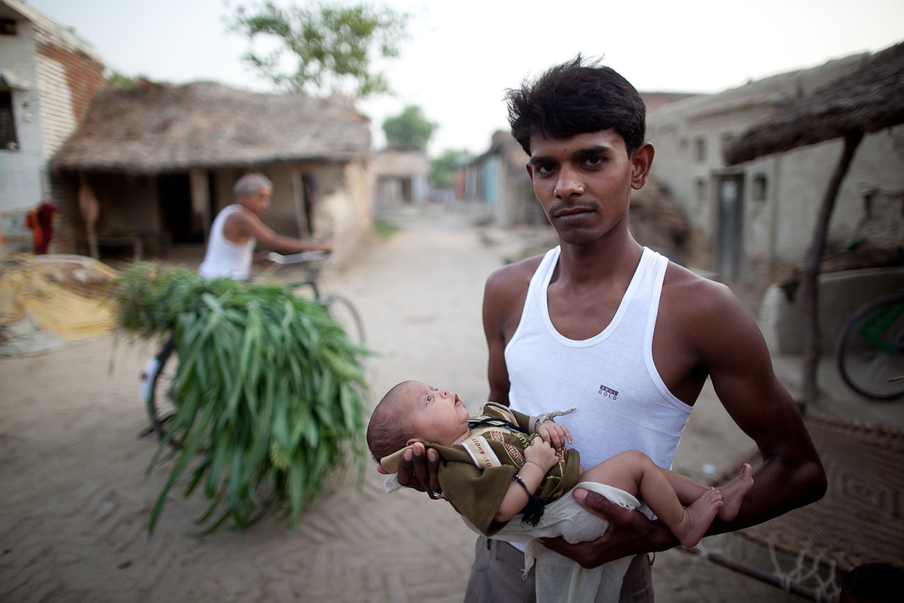 A young Indian man holding his very tiny baby.