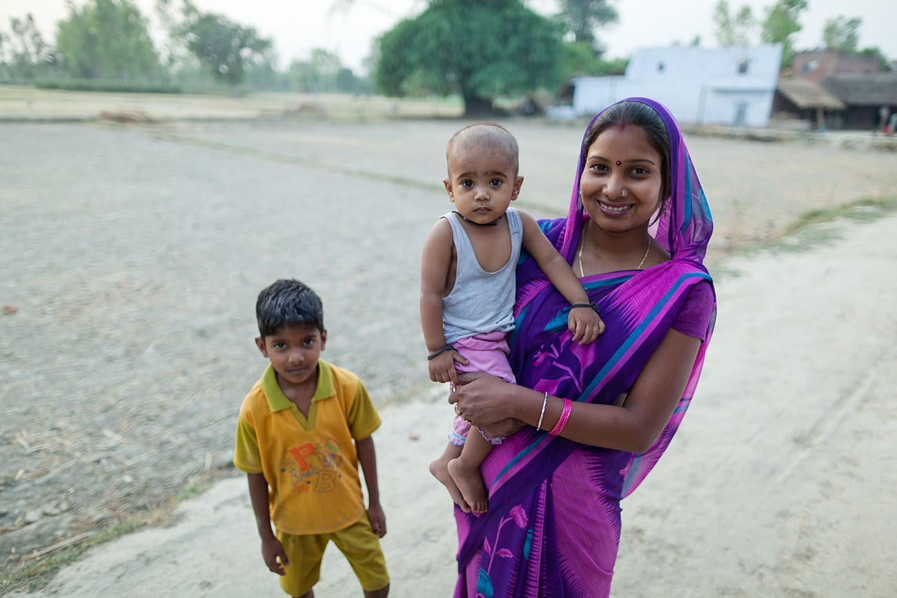 A vibrant young Indian woman holding her baby.
