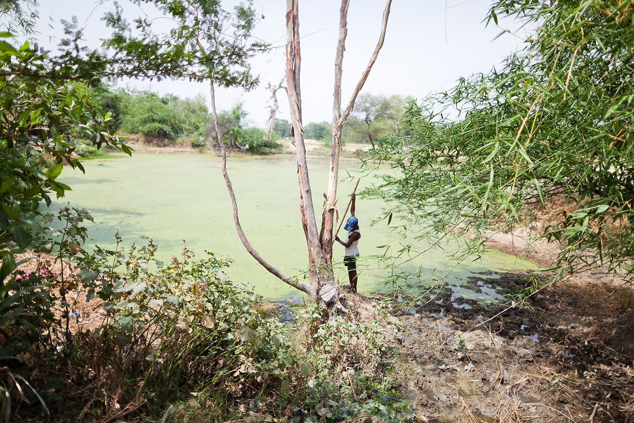 A boy plays on a river bank in India.