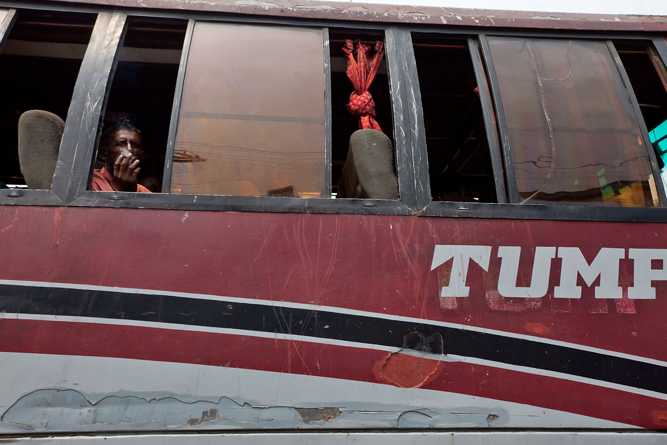 A man looking out the window of a bus in rural India.