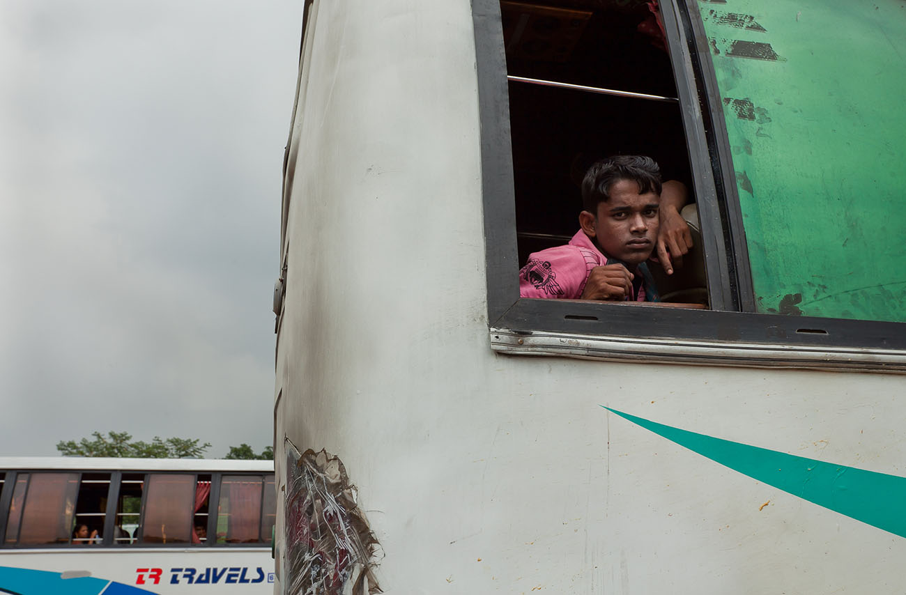 A young man in India looks out from a bus.