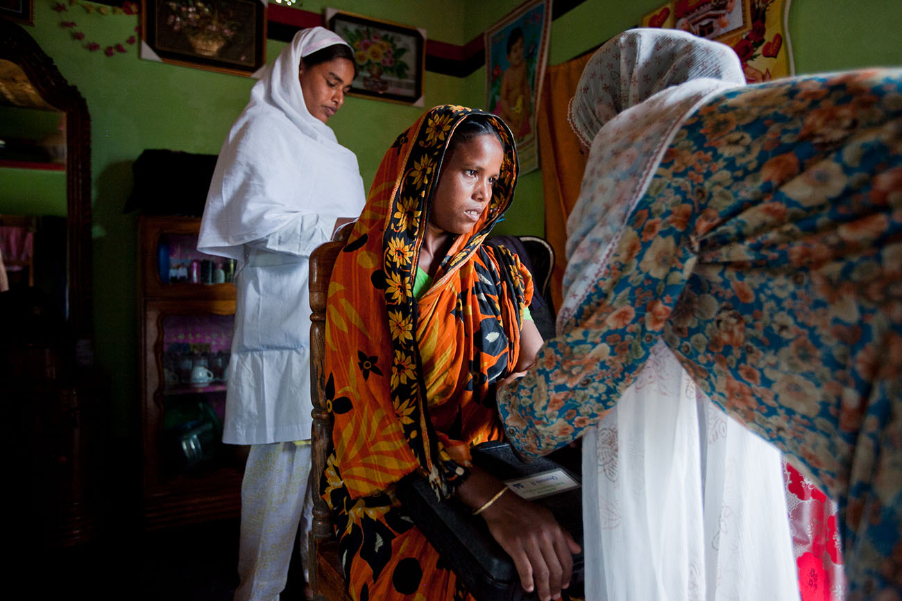 A young woman shows concern as she is attended by nurses in India.