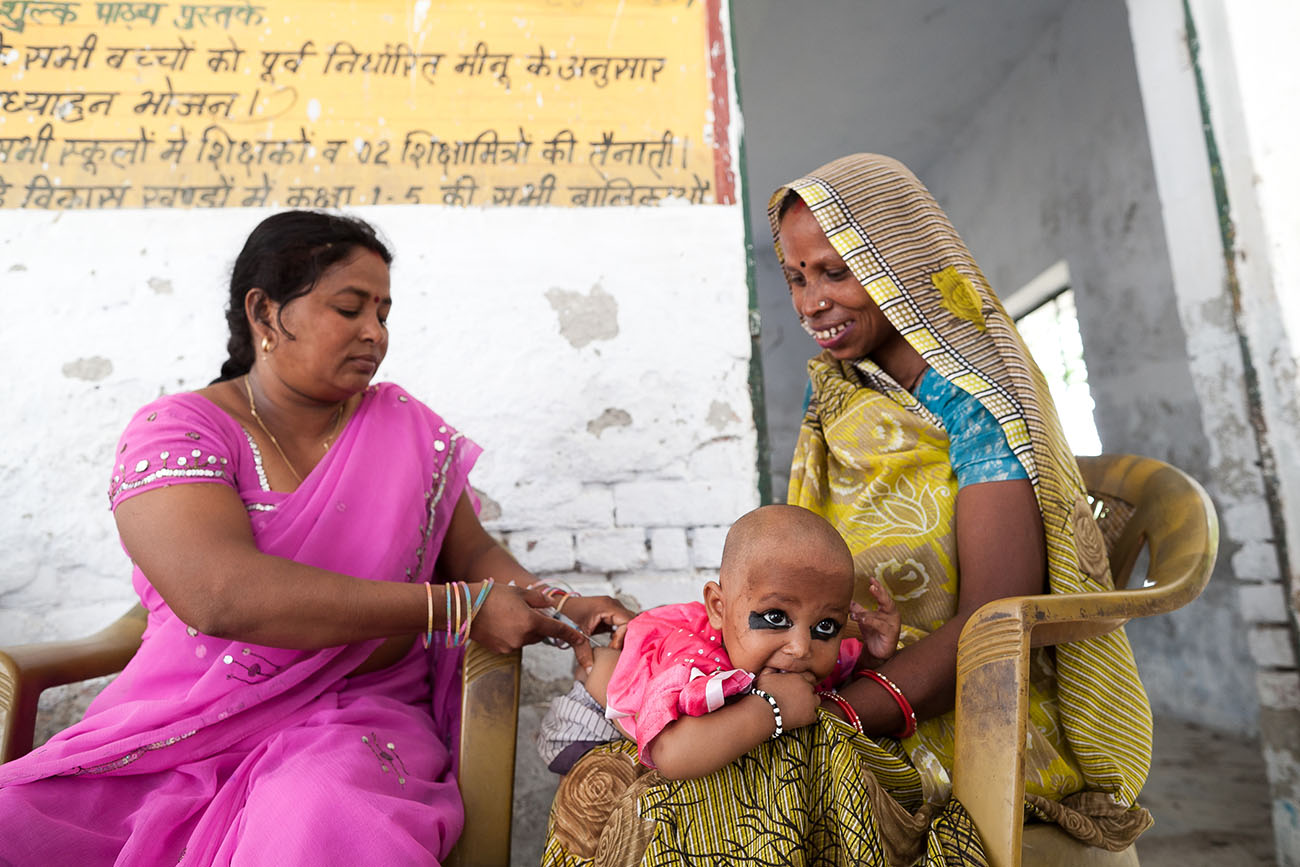 A young mother in India smiles before her baby receives a vaccination.