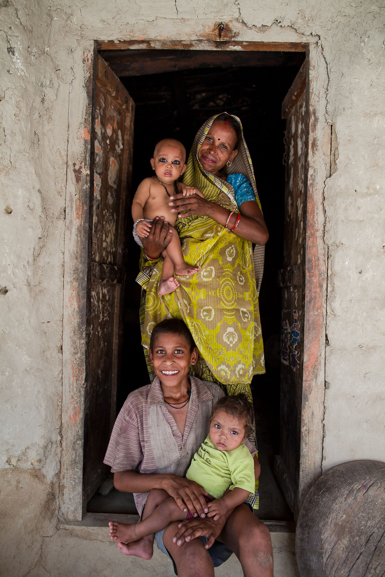Indian mothers and their babies in a doorway.