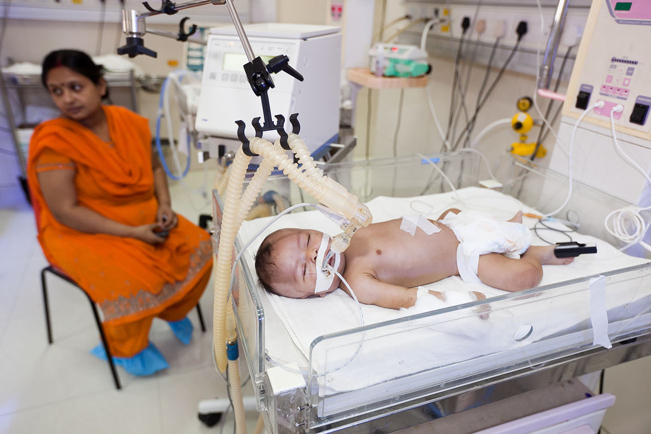 A baby in India, hooked up to a respirator and monitors.