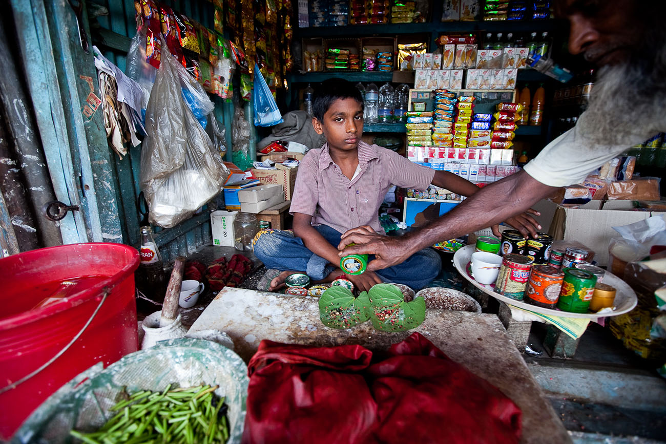 A boy watches over a merchant stall in Bangladesh.