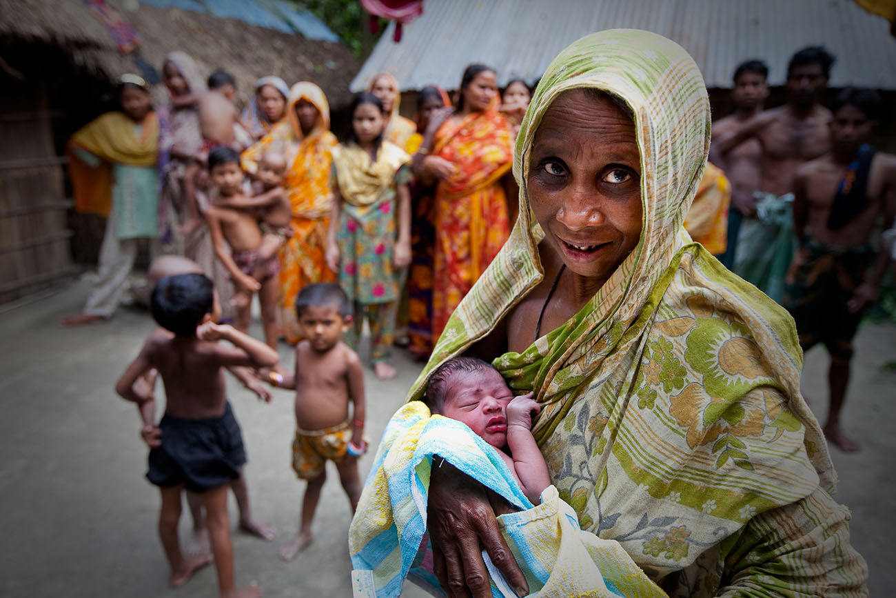 A Bangladeshi baby sleeps in its mother's arms.