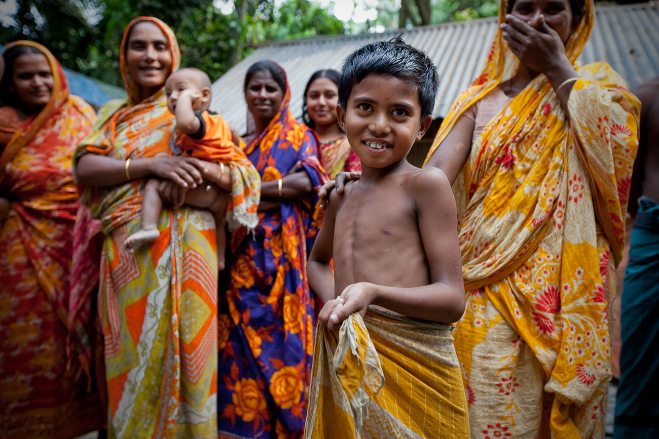 An young boy in Bangladesh grins sheephishly while a group of women watch.