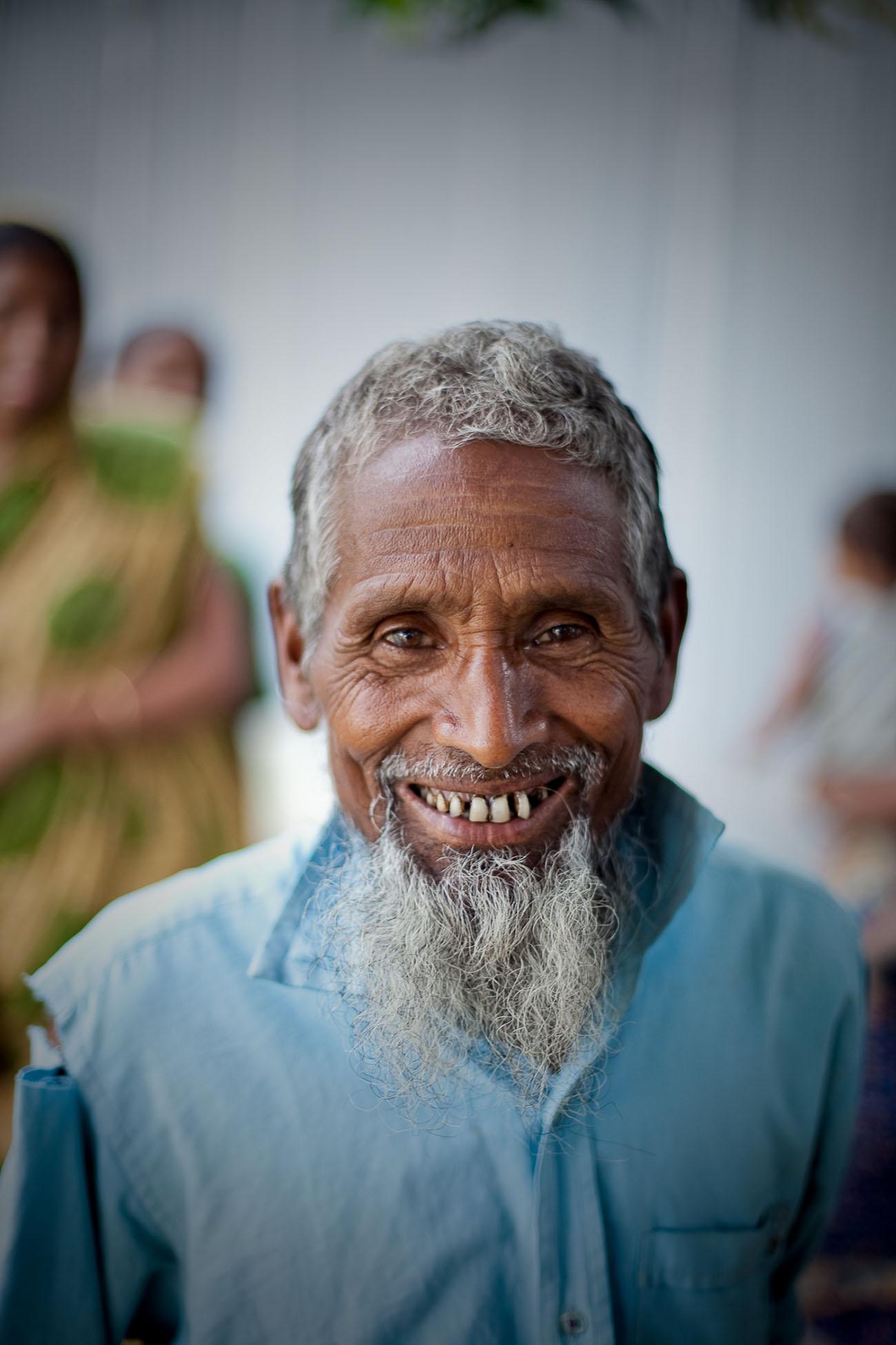 An old Bangladeshi man smiles for a photograph.