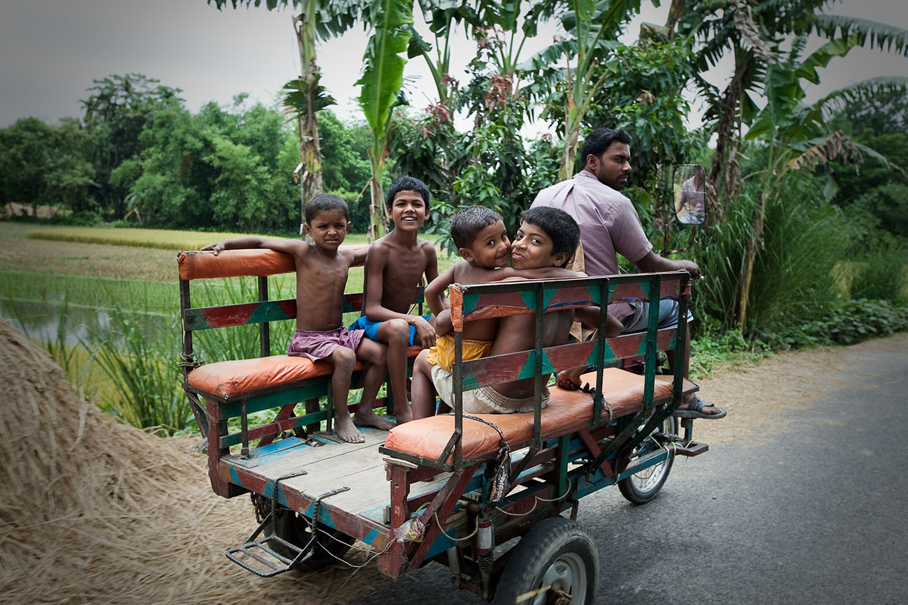 Boys ride on the back of a rickshaw in Bangladesh.