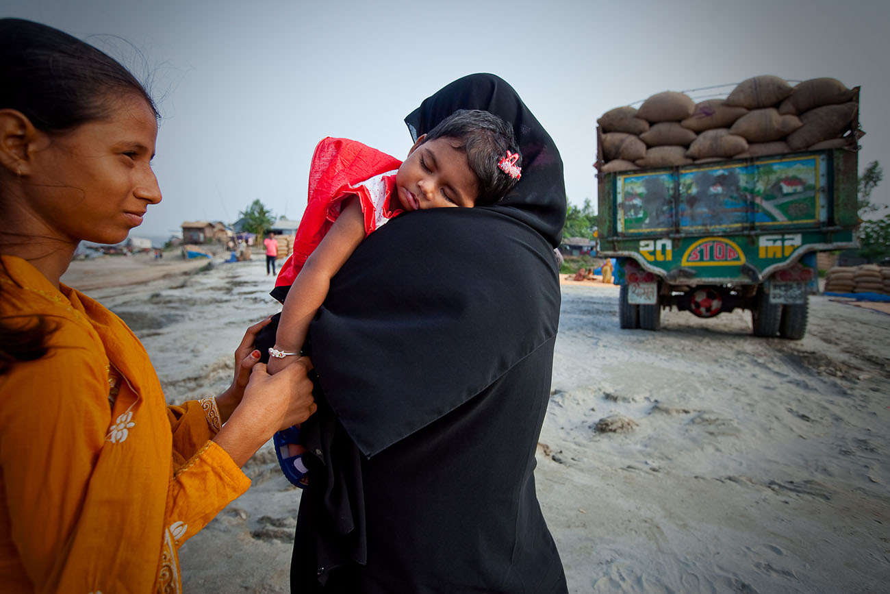A girl sleeps in her mother's arms in Bangladesh.