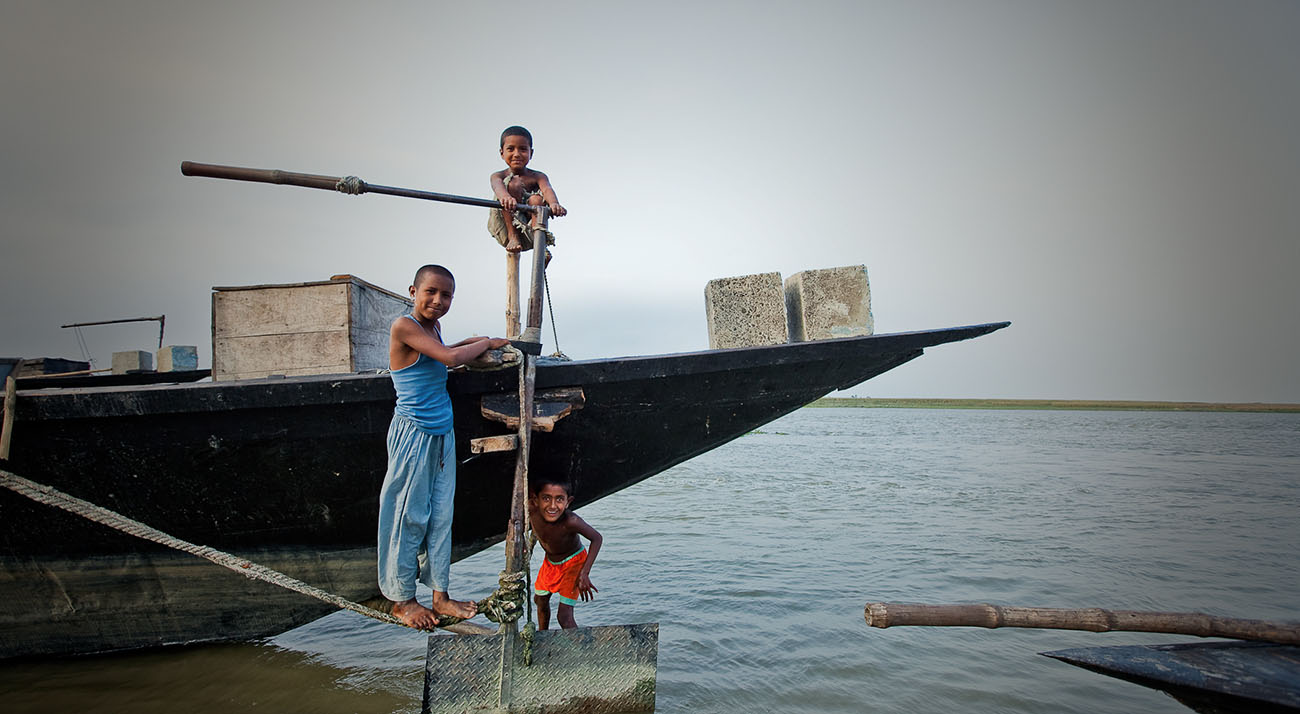 Boys play on a boat in Bangladesh.
