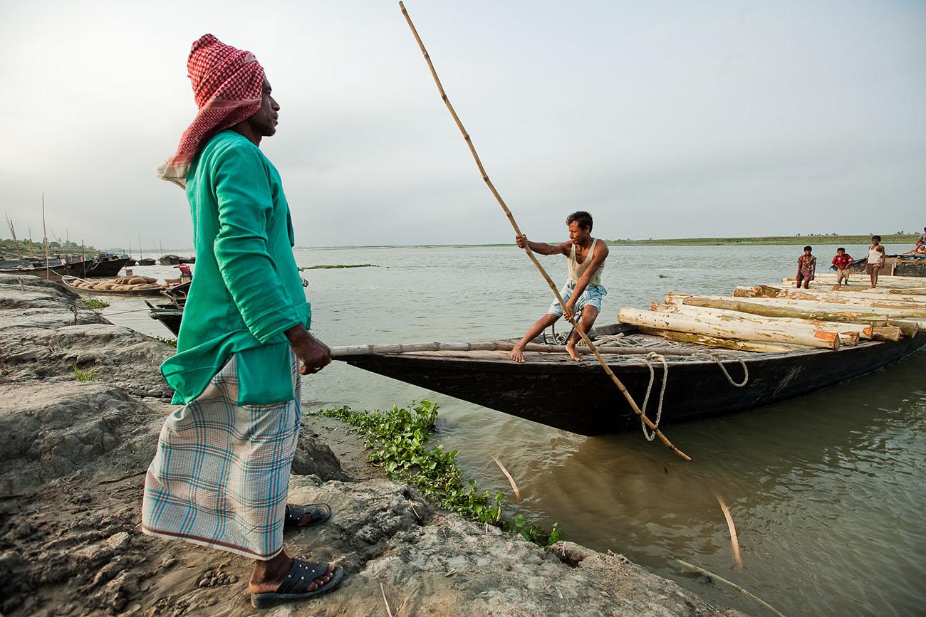 A Bangladeshi man uses a pole to push his boat away from shore.