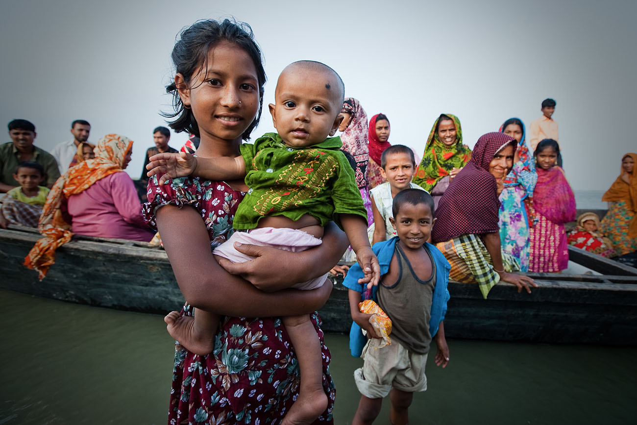 Families sitting on a boat in Bangladesh.