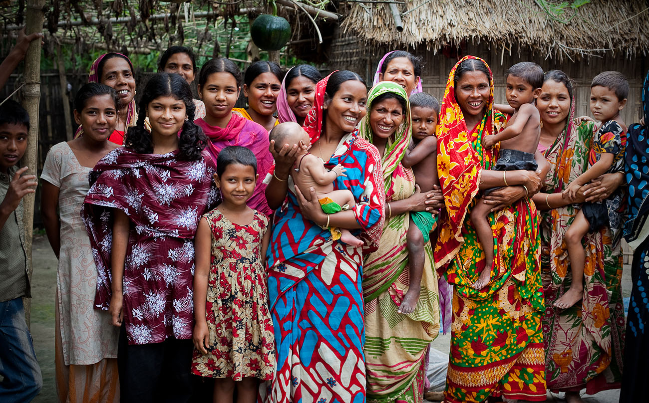 Bangladeshi women pose for a photo, some with their young children.