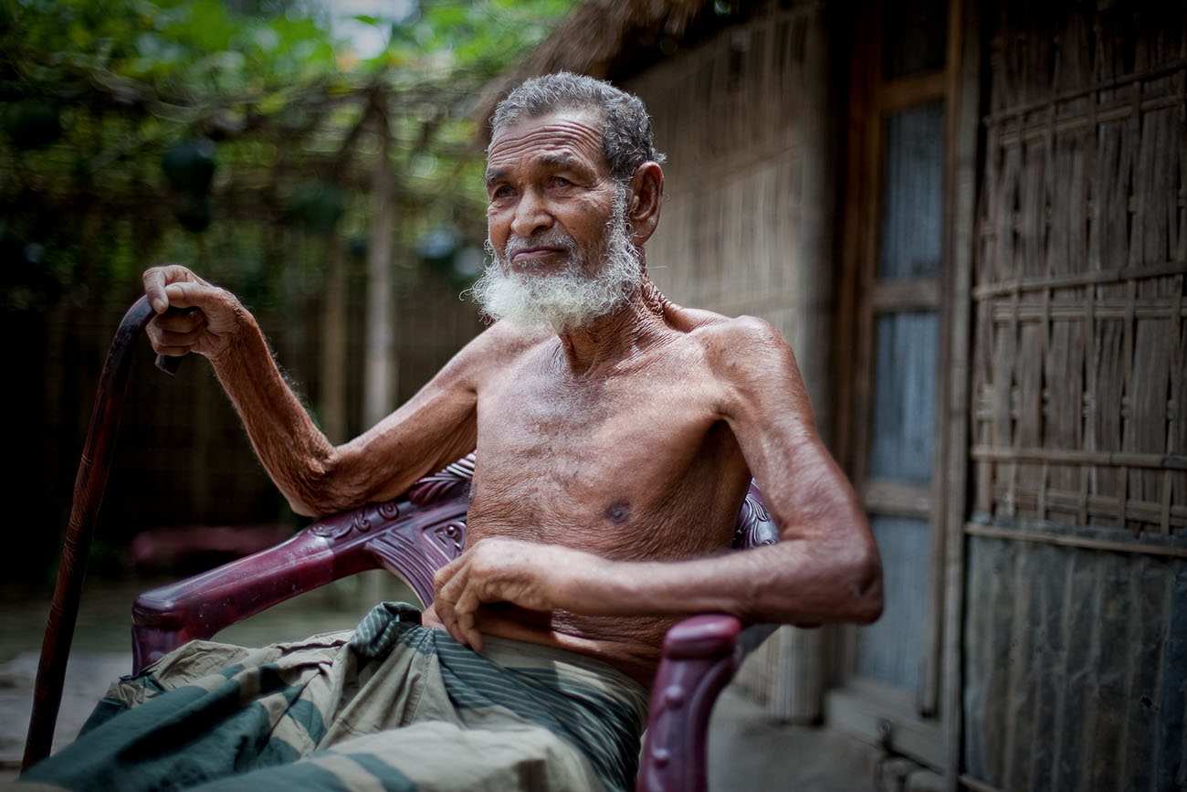 An old man in Bangladesh seated in a fine chair.