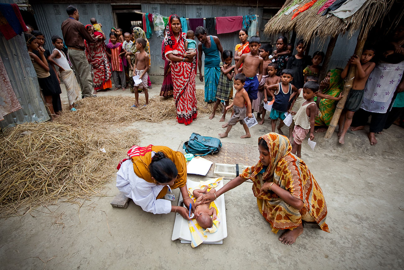 A Bangladeshi baby is being taken care of by a nurse while its mother assists.