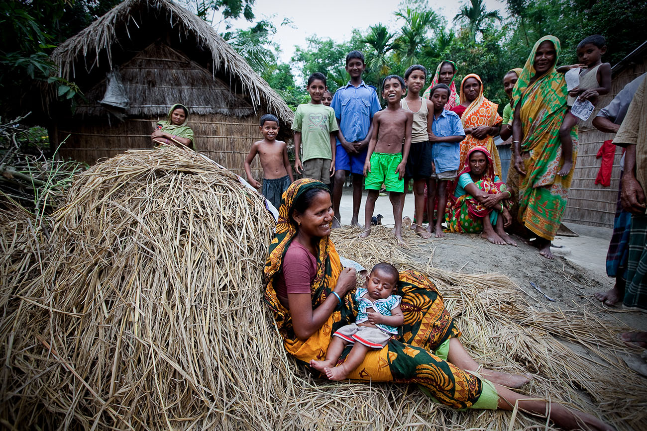 A woman in Bangladesh sits on a pile of straw with her baby.