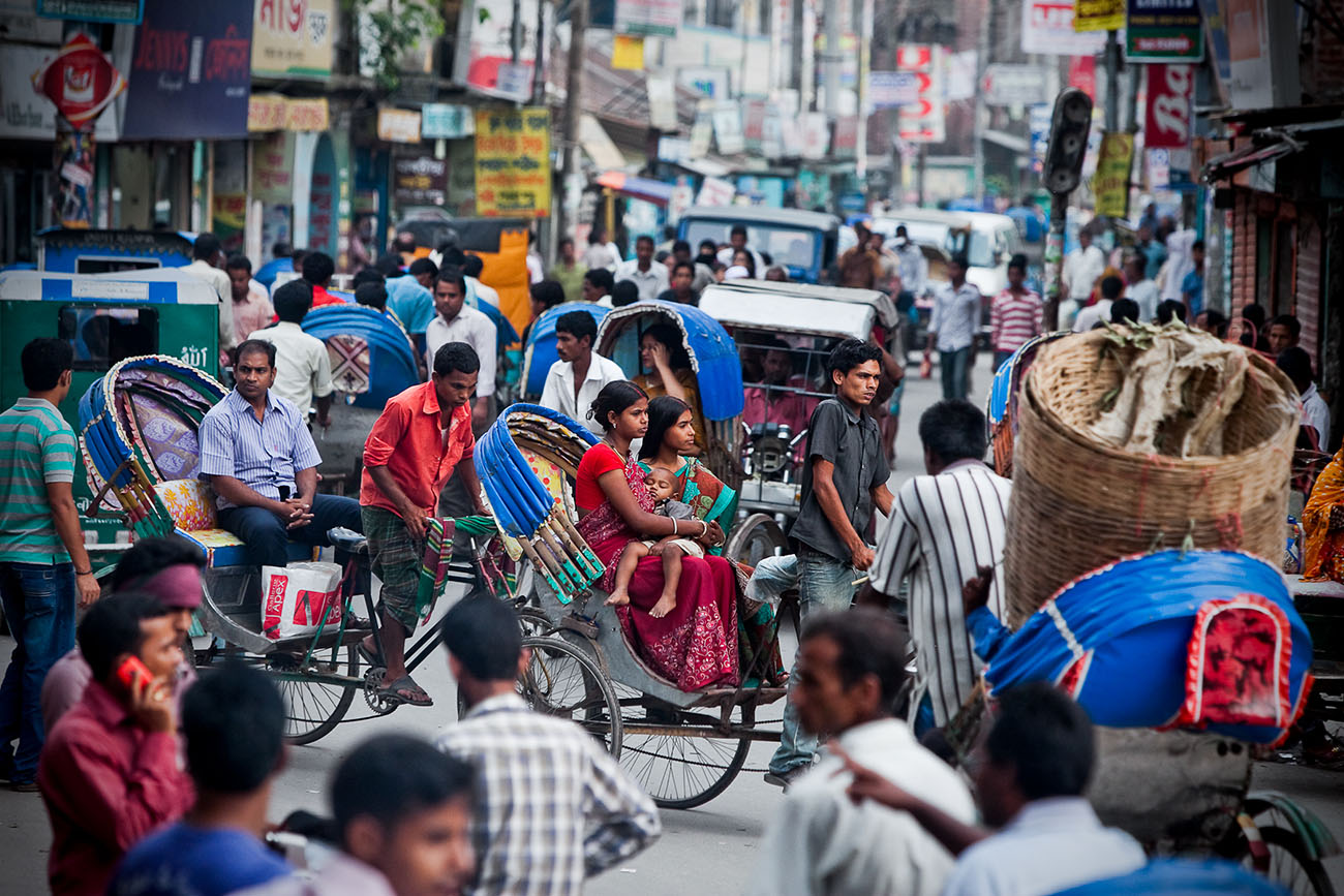Traffic in Bangladesh is comprised of people on foot, bicycle, and a variety of cars.