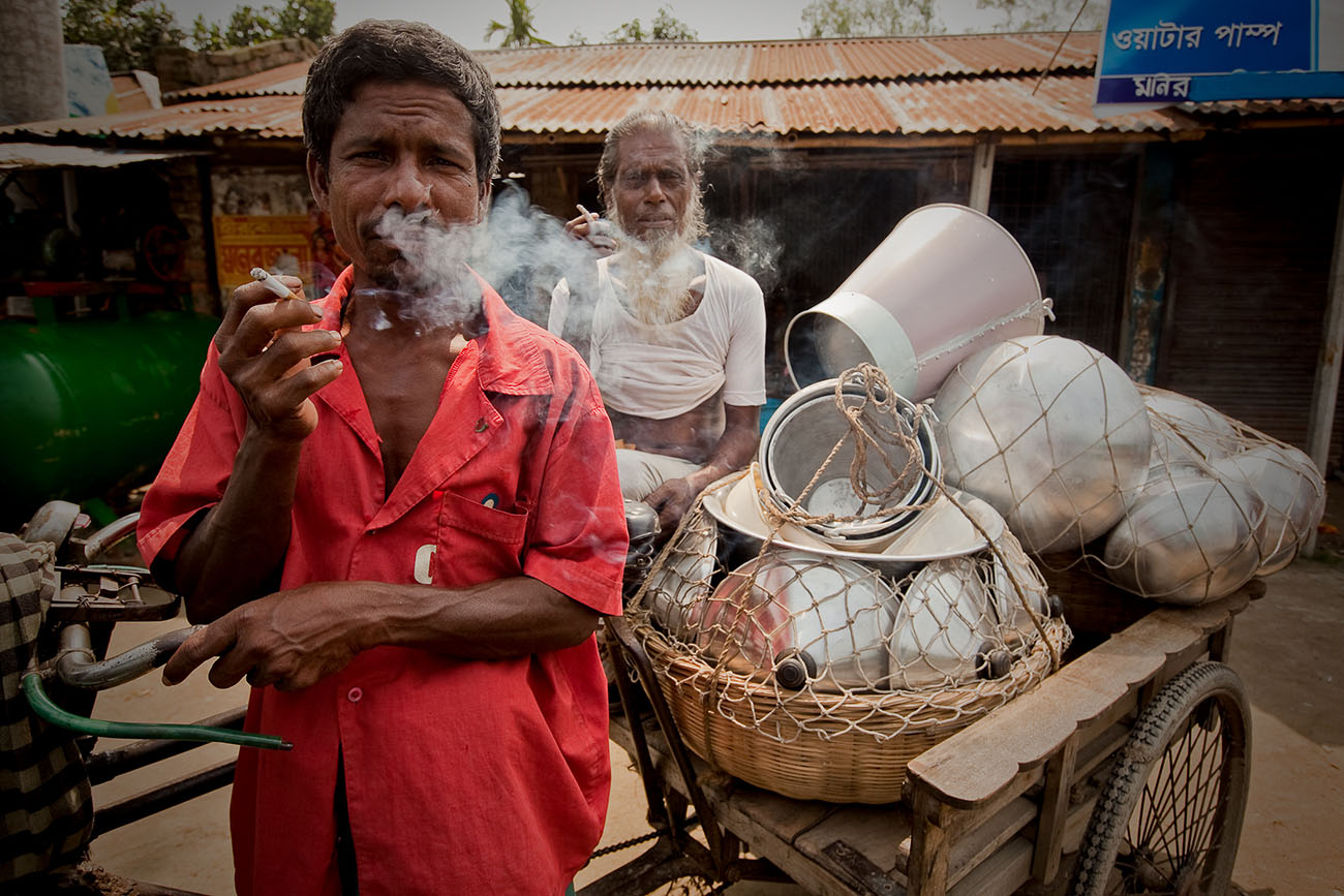 Bangladeshi men pose for a picture while smoking.