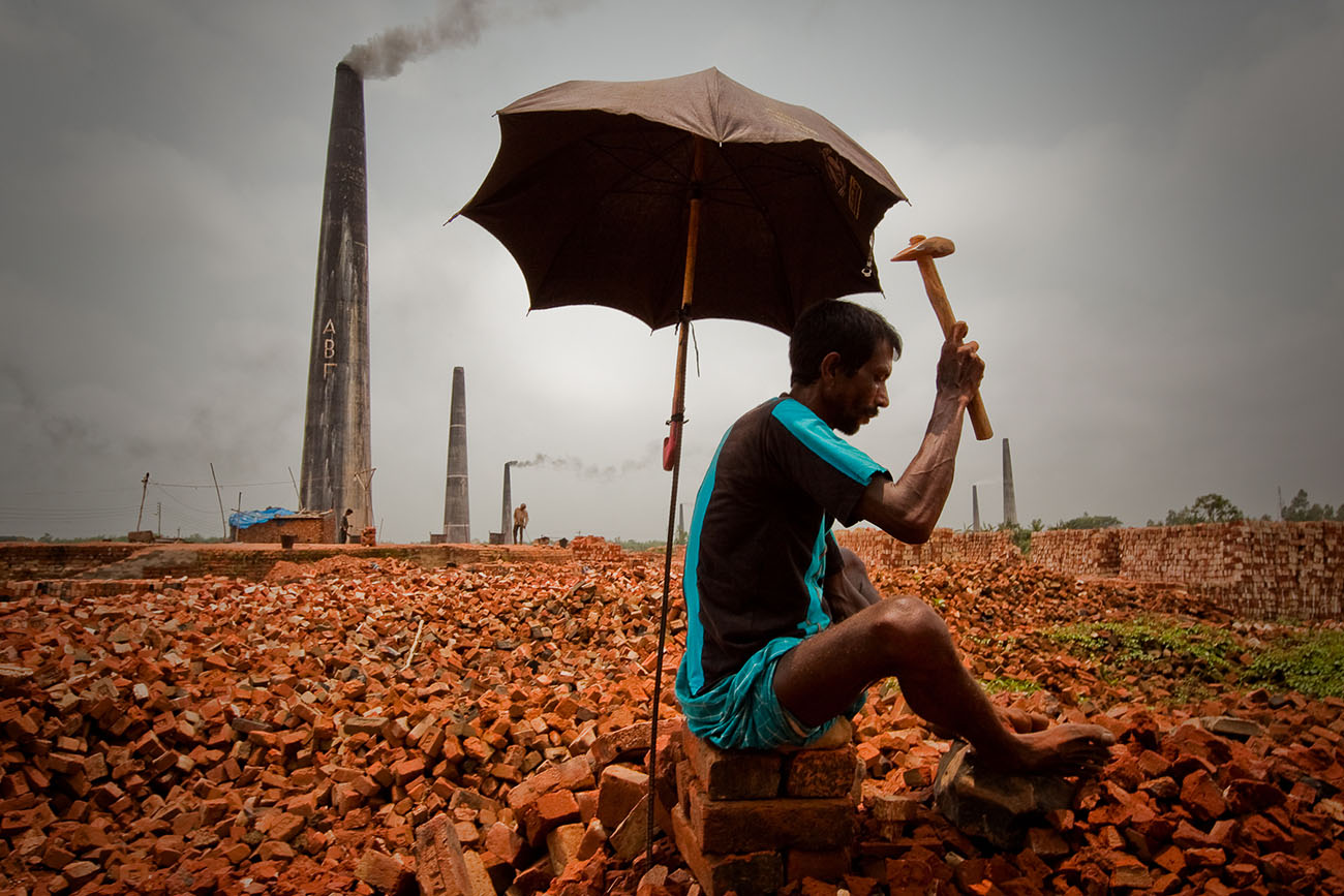 A man in Bangladesh labors over a pile of bricks, breaking them into smaller pieces.