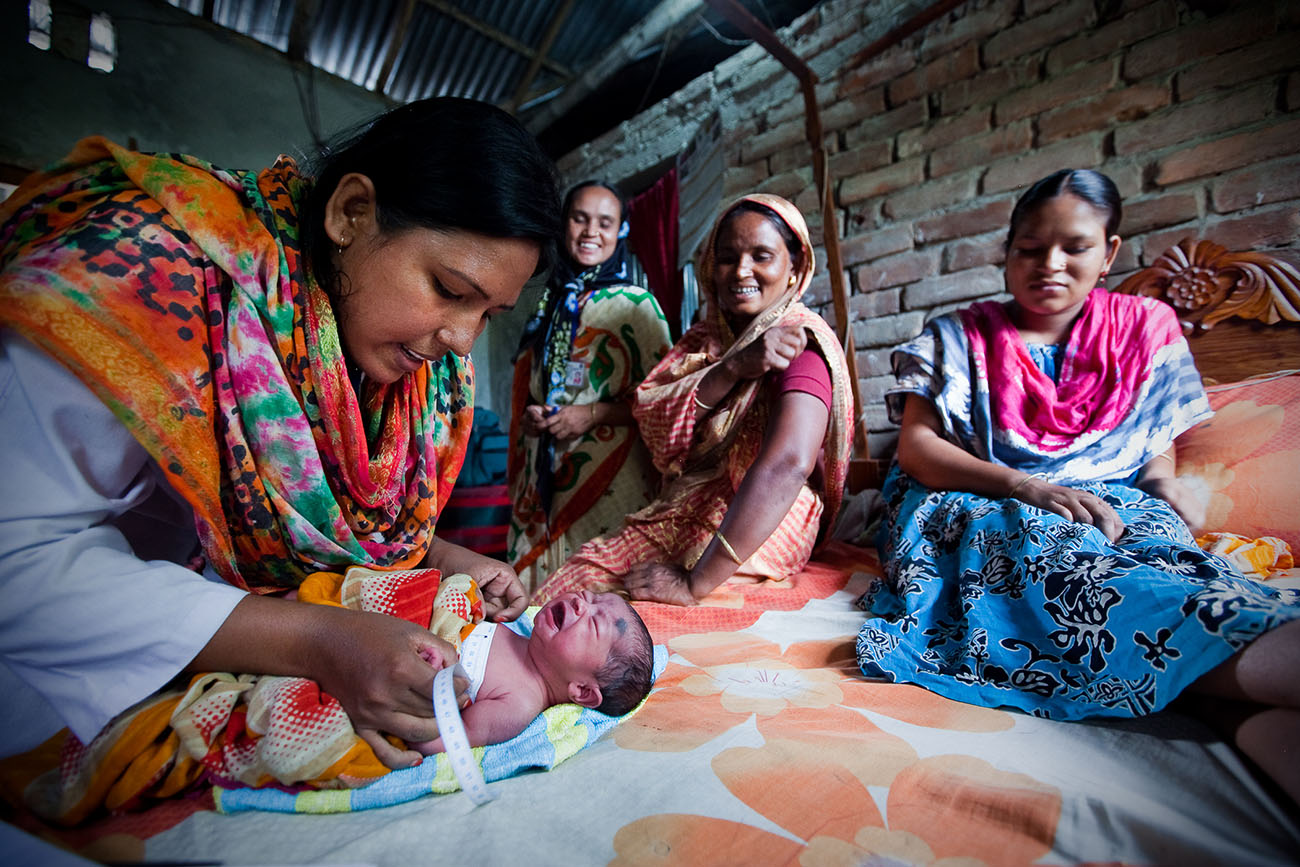 A nurse checks the development of a Bangladeshi baby.