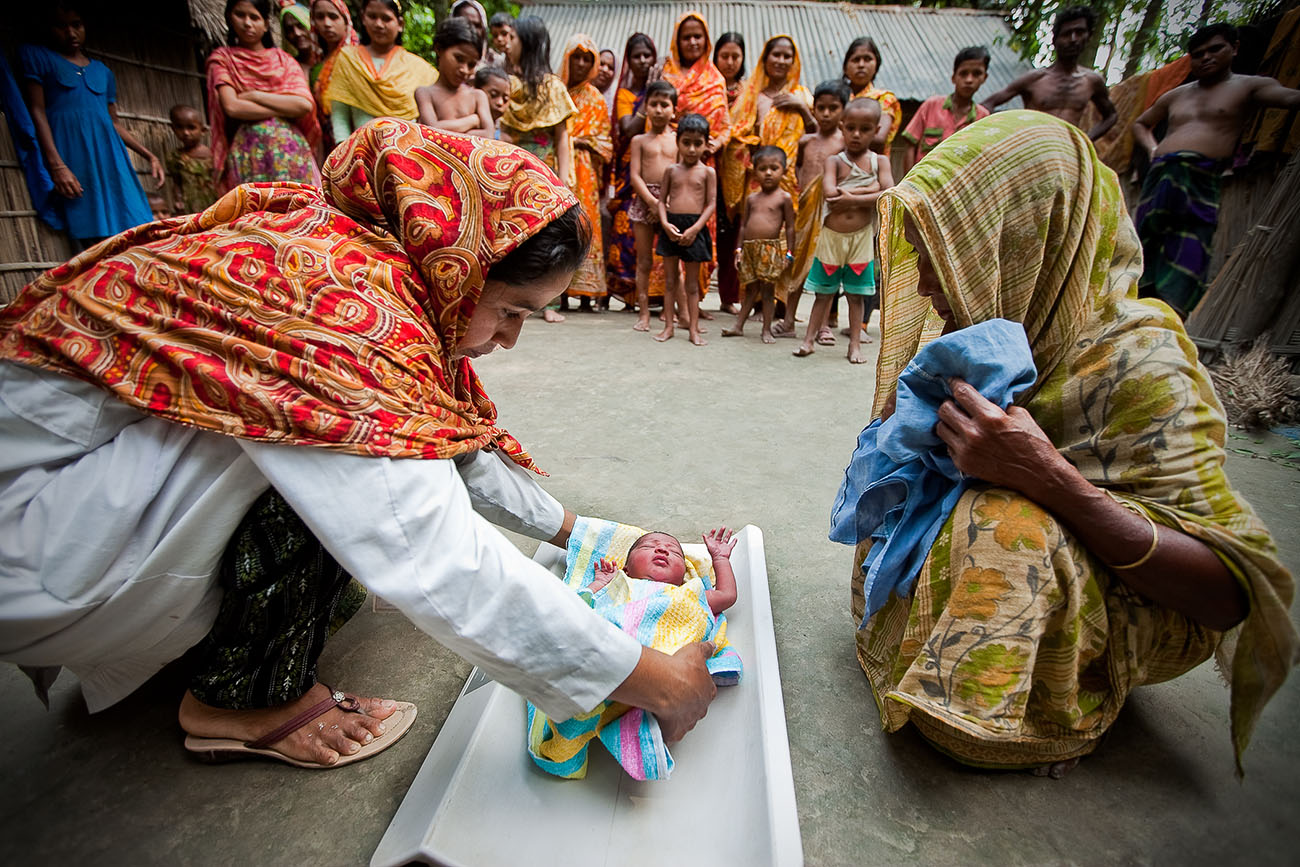 In Bangladesh, a nurse gently weighs a baby on a scale.