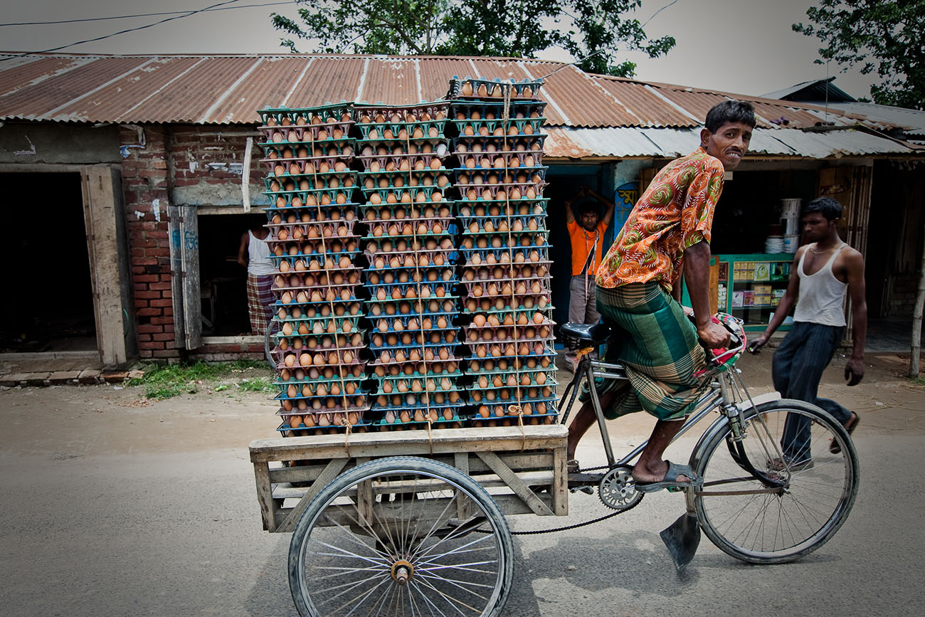 A man transports a large amount of eggs by rickshaw in Bangladesh.