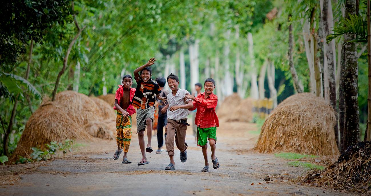 Kids run down a road in Bangladesh.
