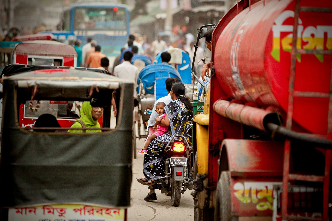 A father, mother, and a baby sit on a motorcycle in traffic in Bangladesh.