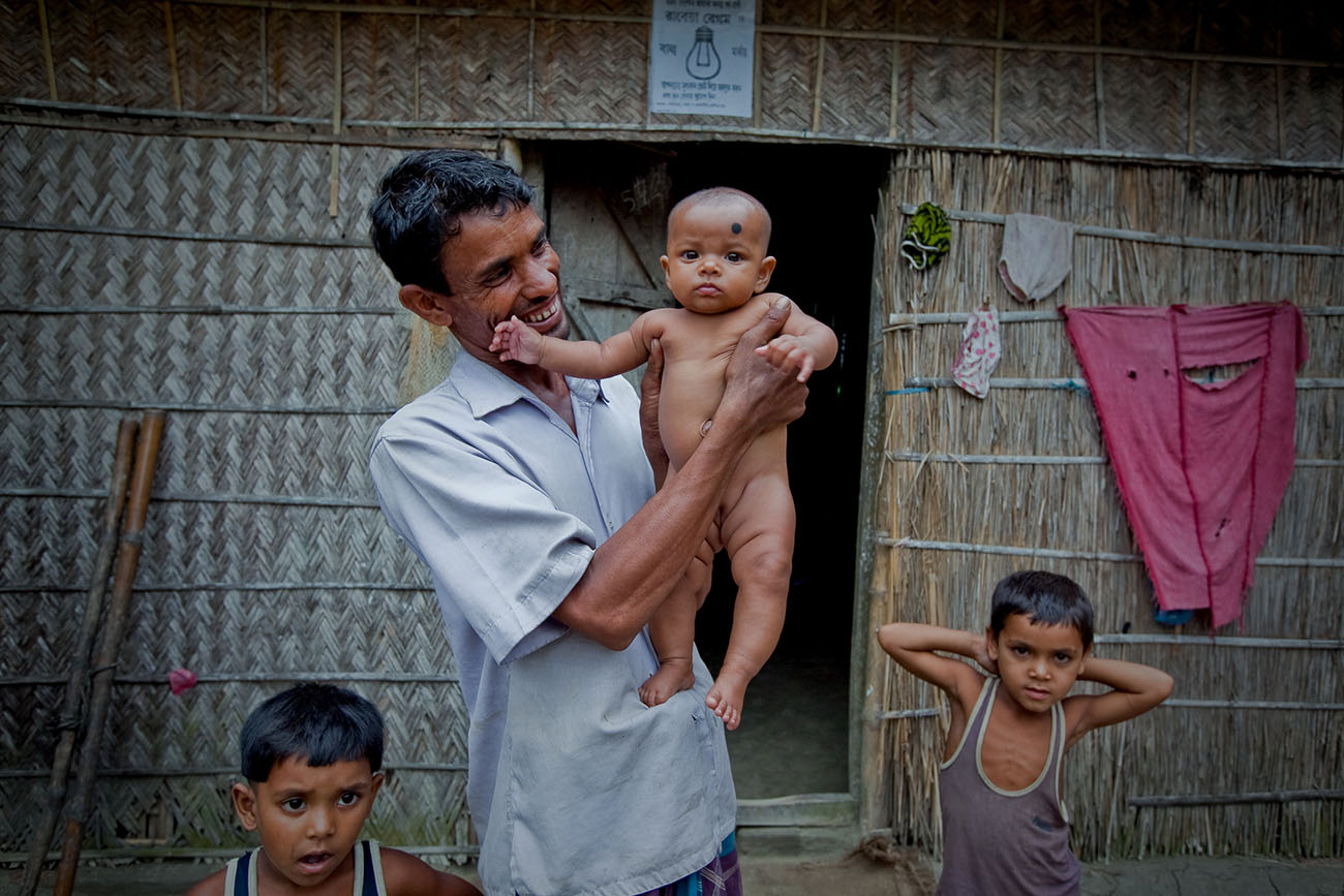 A proud Bangladeshi father holds his daughter for the camera.