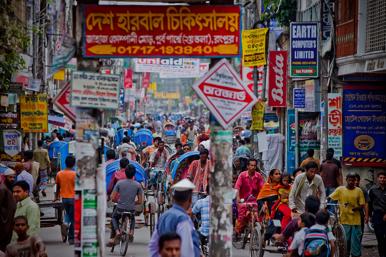 Signs decorate the buildings and posts while people flood the streets on foot and rickshaws in urban Bangladesh.