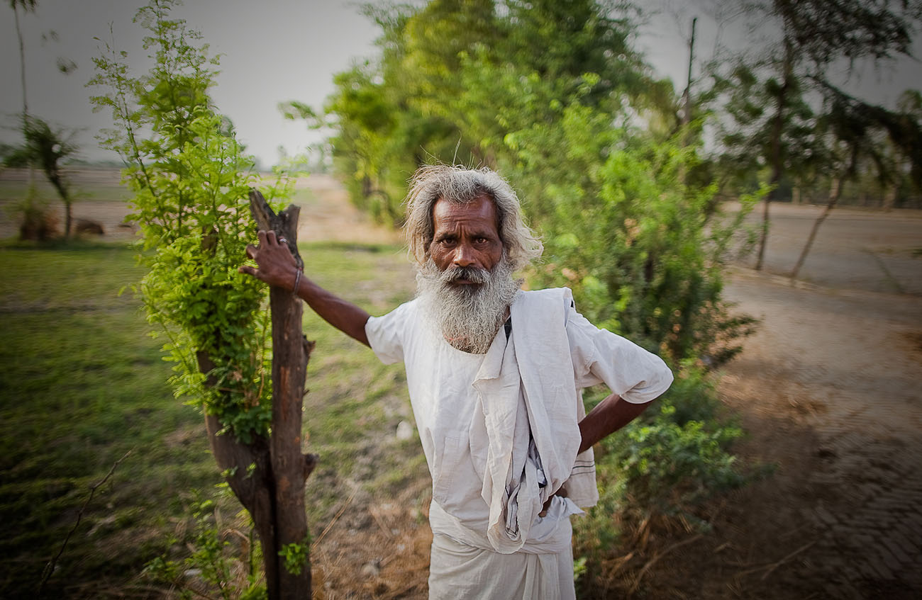 A Indian man poses for a picture.