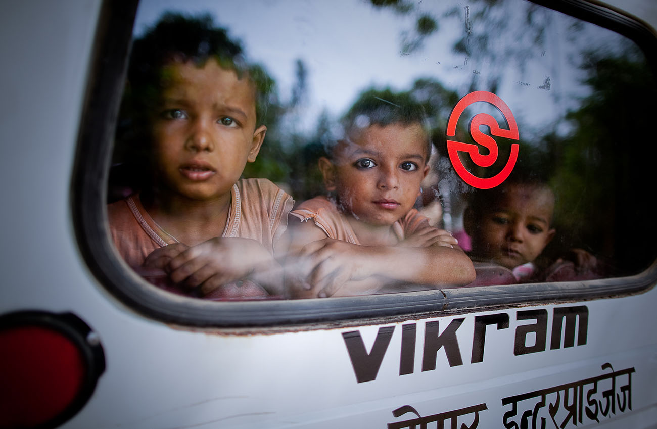 Young boys in India riding a bus.