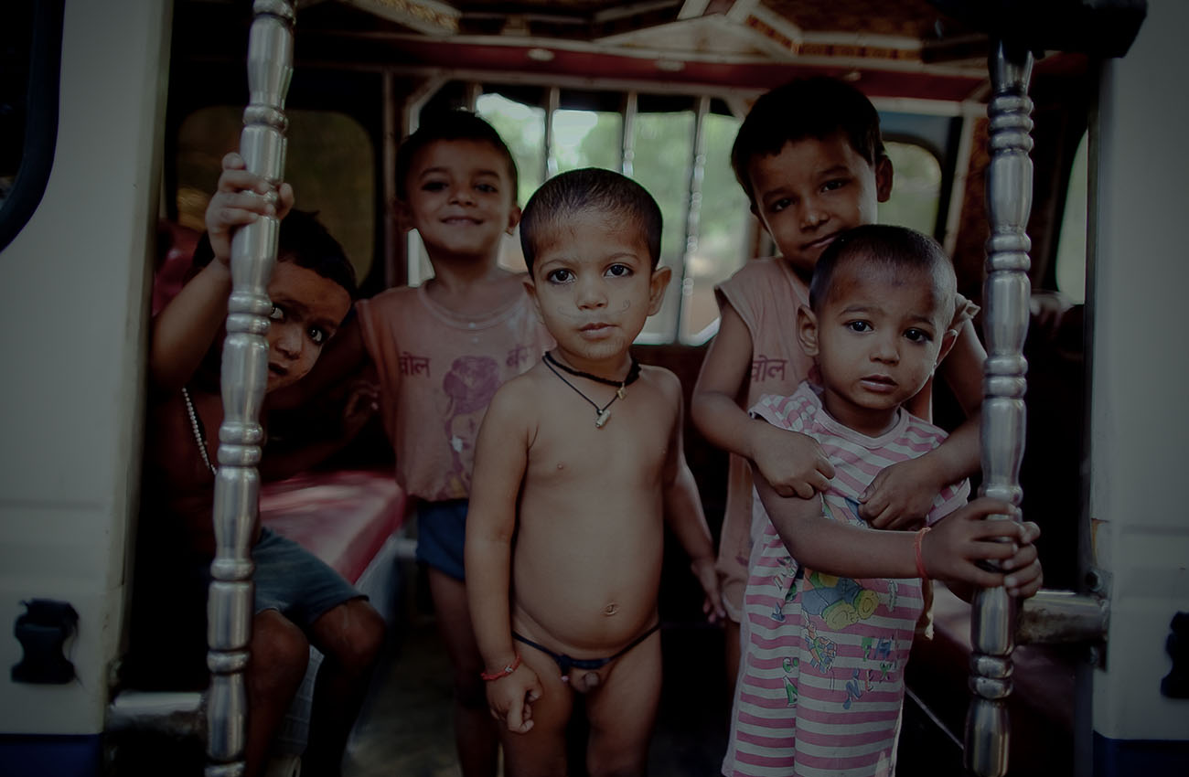A group of young boys standing in the doorway of a bus in India.