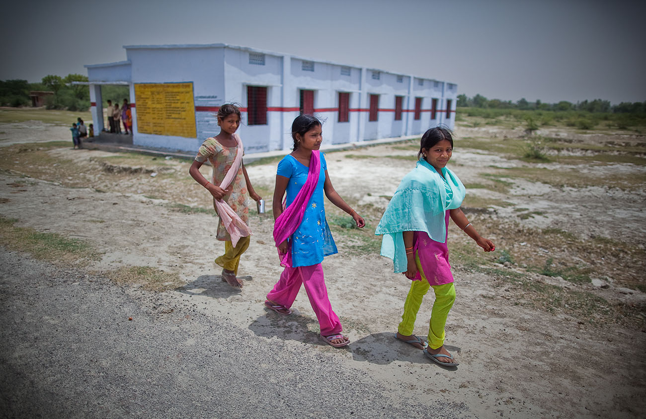 Young Indian girls walking down a road.