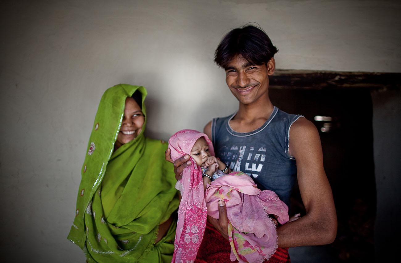 A young Indian family is happy to receive healthcare for the mother and young baby.